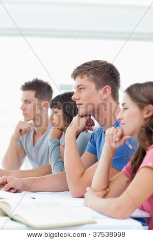 A class of students sitting beside one another and listening
