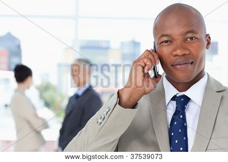 Young serious executive in a suit talking on the phone while his team stands behind him
