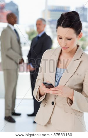 Young serious businesswoman sending a text while executives are talking behind her