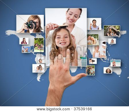 Hand selecting pictures against blue world map background