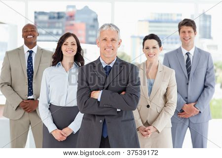 Mature businessman standing upright and crossing his arms in front of his team