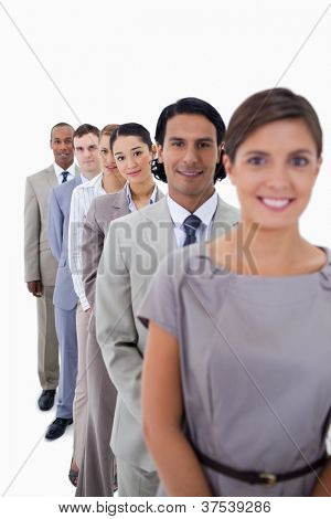 Close-up of co-workers in a single line looking straight with focus on the second woman against white background