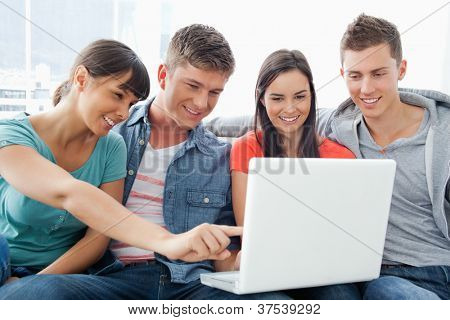 A group of friends smiling as they watch the screen of the laptop with one girl pointing something out