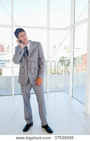 Young serious businessman making a call while looking upwards