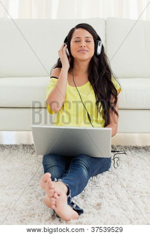 Pretty Latin enjoying music on a laptop while sitting on the floor