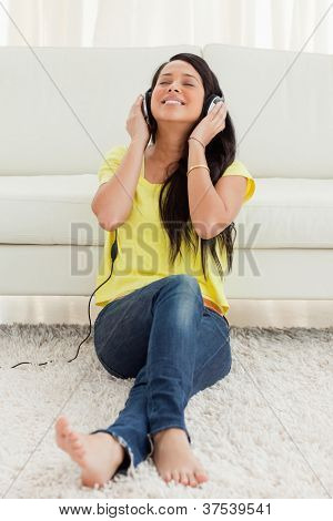 Pretty Latin enjoying music while sitting on the floor