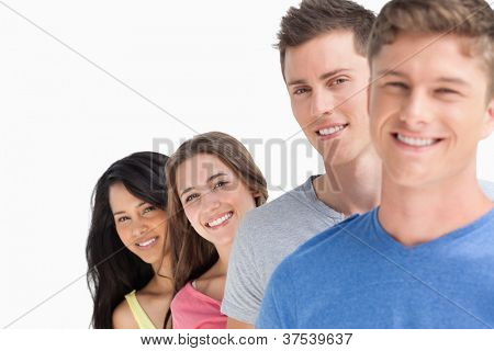 A smiling group of people standing at angle while they all smile and look at the camera