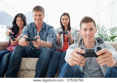 A smiling group of friends playing together on a console while looking into the camera