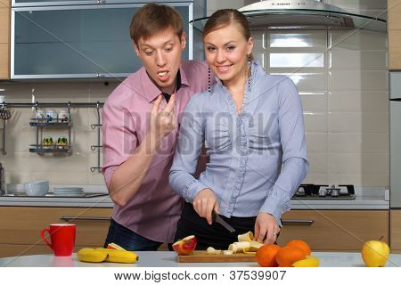 Young woman cutting banana with a sly glance in front of her boyfriend cast an intimidated glance