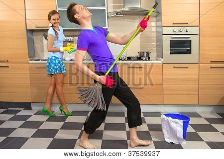 Modern kitchen - woman with sponge and smiling young man cleaning the floor at home and pretend to sing song with mop