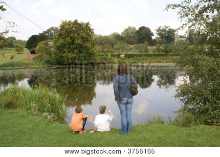 Woman And Children Looking At A Lake.