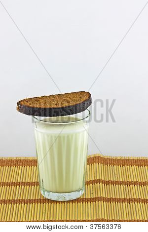 A Piece Of Black Bread On A Glass Of Sour Milk