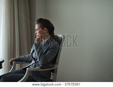 Thoughtful Business Woman Sitting In Hotel Room