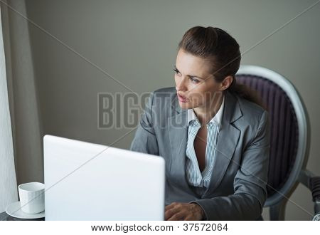 Thoughtful Business Woman In Hotel Room Looking In Window