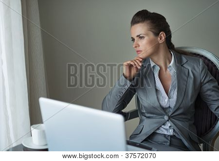 Thoughtful Business Woman Working On Laptop In Hotel Room