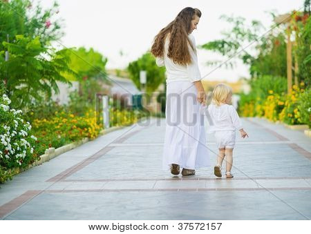 Mother And Baby Walking Outdoors. Rear View