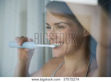Young Woman Brushing Teeth With Electric Toothbrush And Looking