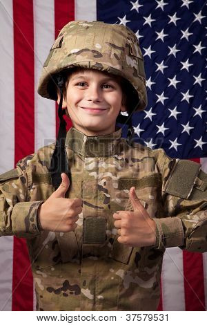 Boy Usa Soldier Is Showing Thumbs Up In Front Of American Flag.