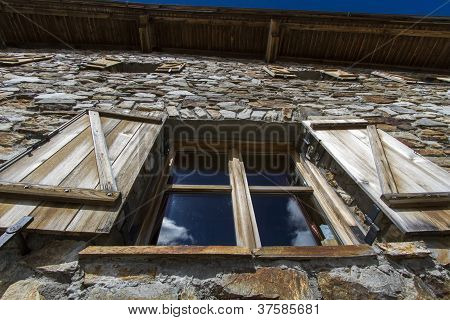 Window of a mountain hut seen in the italian alps