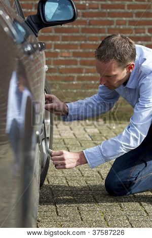 Man Using Duct Tape To Fix Car.