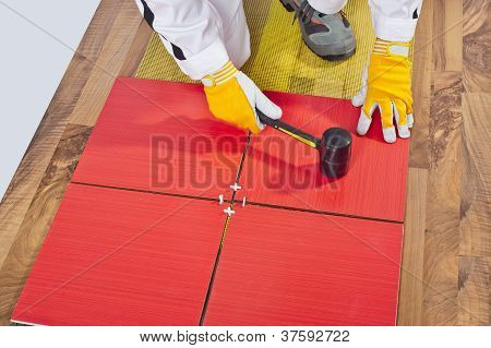 Worker Applies With Rubber Hummer Tile On A Wooden Floor Reinforced Net