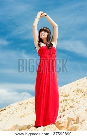 A girl in a red dress posing on a sand dune.