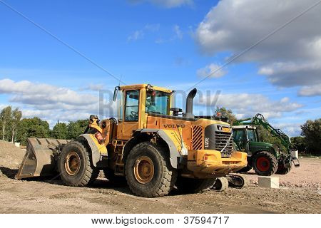 One Loader Excavator And Grapple Tractor At Construction Site