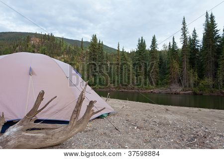 Tent at river in remote Yukon taiga wilderness