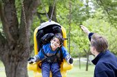 image of babysitting  - Father pushing disabled son on yellow handicap swing - JPG