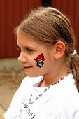 picture of face painting  - A young girl shows off a butterfly which has been painted on her face at a craft fair - JPG