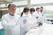 Chemist using tablet pc in busy lab