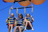 image of parasailing  - Father and Twin Daughters Parasailing Against a Blue Summer Sky - JPG