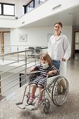 foto of neck brace  - Child in neck brace being pushed in wheelchair by doctor in hospital corridor - JPG