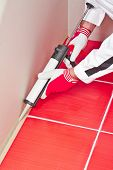 foto of hermetic  - Worker Applies Silicone Sealant On Corner Wall Tiles - JPG