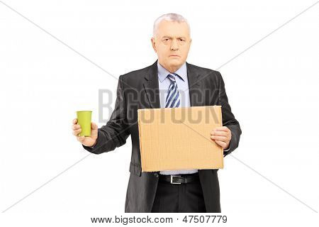 Bankrupted mature businessman holding a piece of cardboard and cup begging, isolated on white background