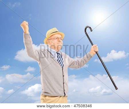 Happy senior man holding a cane and gesturing happiness outside on a sunny day