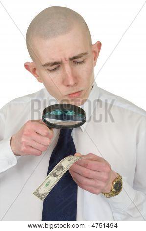 Hombre estudiando un dinero falsificado