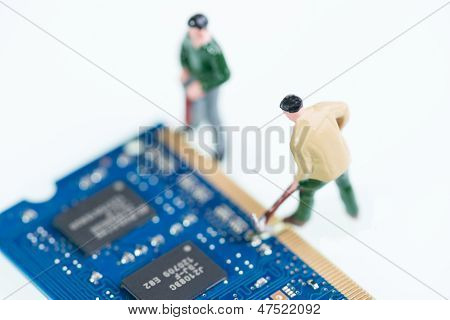 Miniature Workmen Working On Computer Component Top View