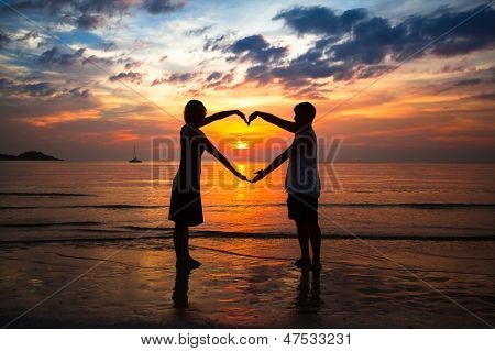 Couple holding hands heart-shaped on the sea beach at sunset
