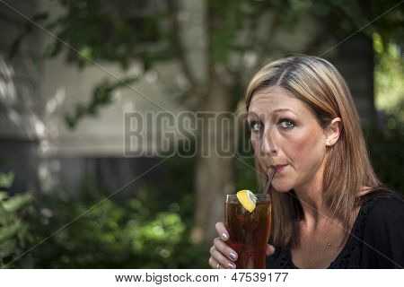 Blonde Woman With Beautiful Blue Eyes And Glass Of Iced Tea