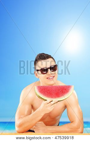 Young man laying on a towel and eating a slice of watermelon on a beach, next to the sea