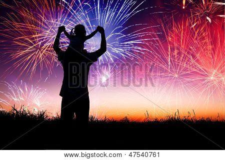 Vater mit Kind auf dem Hügel stehen und beobachten das Feuerwerk
