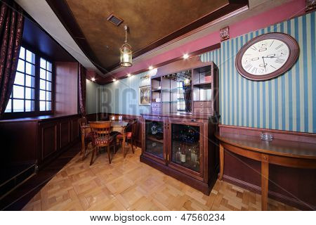 Bar in wooden closet and table in english cigar room for rest.