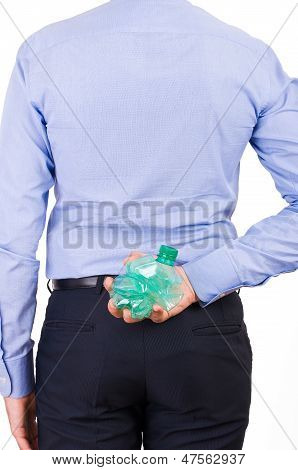 Businessman holding crushed bottle behind his back.