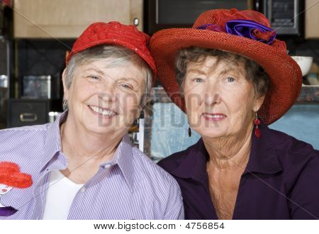 Two Senior Women Wearing Red Hats