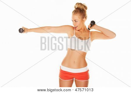 Beautiful fit young woman with a shapely athletic figure exercising with dumbbells extending her arms in front of her, isolated on white