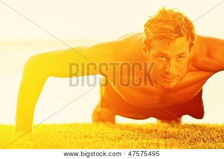 Flexões de homem do esporte fitness. Atleta masculino exercendo pressão lá fora no sol ensolarado. Apto sem camisa