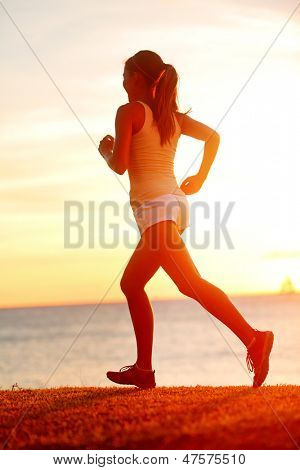 Jogging athlete woman running at sun sunset beach. Fitness runner girl training outside by the ocean sea in beautiful sunset or sunrise in full body length in summer.