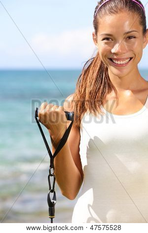 Fitness girl training at beach with elastics resistance bands. Fit sporty woman strength training biceps outdoors using elastic. Mixed race Asian Caucasian sport model outside working out.