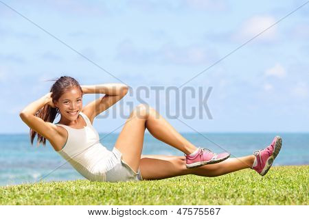 Exercising fitness woman doing sit ups outside during exercise training. Happy fit girl doing side crunches with elevated legs while smiling happy. Beautiful mixed race Asian female model.